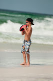 Cute little boy catching football on beach. Royalty Free Stock Photos