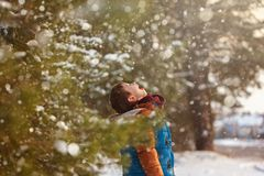 Cute little boy catching snowflakes with his tongue while walking in winter sunny day. Cute little boy catching snowflakes with his tongue while walking in Royalty Free Stock Photos