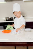 Cute little boy chef getting ready for dinner. Wiping and cleaning the plates before placing them on the kitchen table Royalty Free Stock Photography