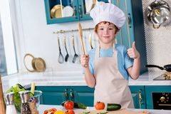 Cute little boy in chef hat and apron smiling at camera and showing thumb up. In kitchen Stock Photos