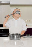Cute little boy chef tasting the recipe. Sipping from a large stainless steel ladle as he samples the food Stock Images