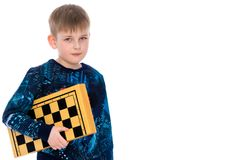 Little boy with a chessboard. Cute little boy with a chessboard. The concept of children`s and developing games in chess, checkers.  on white background Royalty Free Stock Photo