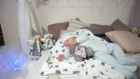 Cute little boy, child hugging a toy while sleeping, Small child sleeps, baby lying on the bed in the sliders and cap stock footage