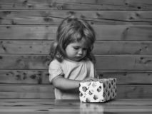 Boy opens box with cakes. Cute little boy child with long blond hair opens colorful paper box with sweet cakes dessert at wooden table stock photography