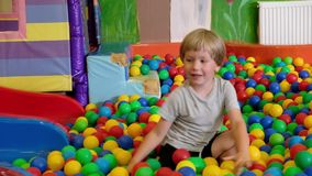 Cute toddler boy, child, playing in colorful balls in children playground, indoors stock video