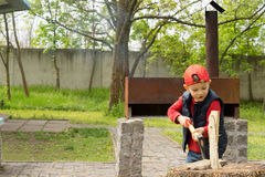 Cute little boy chopping kindling Royalty Free Stock Image
