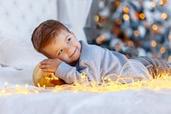 A a cute little boy with a christmass toy ball in front of the christmas tree on the bed. love, happiness concept stock image