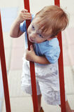 Cute little boy climbing through fence Royalty Free Stock Image