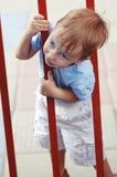 Cute little boy climbing through fence Royalty Free Stock Image