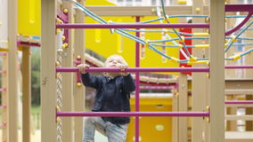 Cute little boy climbing on a jungle gym Royalty Free Stock Image