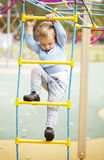 Cute little boy climbing on a jungle gym Royalty Free Stock Images