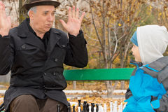 Cute little boy confronting his grandfather. Who is playfully protesting his innocence with his hands raised in the air as they play a game of chess on a park Royalty Free Stock Photo