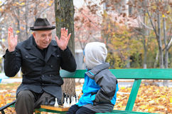 Cute little boy confronting his grandfather who is playfully Stock Images