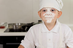 Cute little boy cook with a face full of flour stock photo