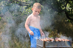 Cute little boy cooking the meat over the fire Royalty Free Stock Images