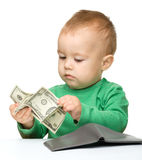 Cute little boy is counting money. Isolated over white Stock Image