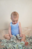 Cute little boy is counting money. Hundreds of dollars Royalty Free Stock Photography