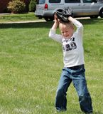 Cute little boy covering his head with baseball glove. Adorable small male child playing catch and lost sight of the ball so he is closing his eyes and covering stock images