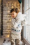 Cute little boy on Cristmas lights background playing with fake snow stock photography
