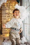 Cute little boy on Cristmas lights background playing with fake snow stock image
