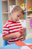Cute little boy cutting paper shapes in classroom Stock Images