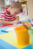 Cute little boy cutting paper shapes in classroom Royalty Free Stock Photos