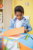 Cute little boy cutting paper shapes in classroom Stock Photos