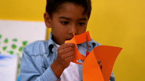 Cute little boy cutting paper shapes in classroom