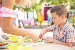 Cute little boy cutting shapes out of colored paper. Being creative, developing imagination, creativity, do it yourself concept royalty free stock image
