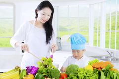 Boy cuts vegetables and mother stirs salad. Cute little boy cutting vegetables while his mother stirring salad on a bowl, shot in the kitchen at home Royalty Free Stock Photo