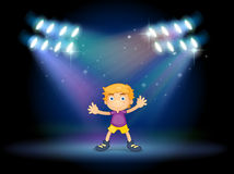 A cute little boy dancing in the middle of the stage Royalty Free Stock Photos