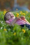 Cute little boy in a dandelion field, having fun Stock Photos