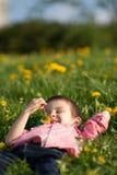Cute little boy in a dandelion field, having fun Royalty Free Stock Image