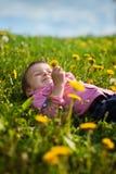 Cute little boy in a dandelion field, having fun Stock Photo