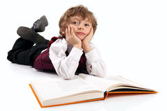 Cute little boy daydreaming while reading book. Over white background in studio stock images