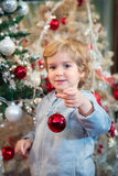 Cute little boy decorating Christmas tree. Royalty Free Stock Photo