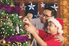 Cute boy decorates a fir tree with father Stock Image