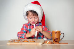 Cute little boy decorating the gingerbread cookies Stock Photo