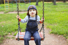 Cute little boy in denim overall swinging on playpit Stock Photography
