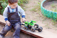 Cute little boy in denim overalls playing in sandbox Royalty Free Stock Photography