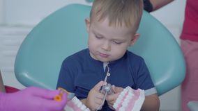 Cute little boy in the dentist office playing with the jaw mock. Carefree child visiting doctor. Dental treatment. The cute little boy in the dentist office stock footage