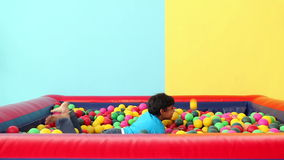 Cute little boy diving into ball pool stock video footage