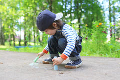 Cute little boy drawing chalk on the ground Royalty Free Stock Photos