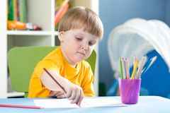 Cute little boy is drawing with color pencils in nursery stock image