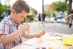 Cute little boy drawing with colorful paints in fall park. Creative child painting on nature. Outdoors activity for toddler kid. Talented toddler painter stock image