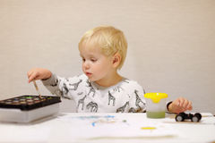 Cute little boy drawing with colorful paints at home Royalty Free Stock Photos