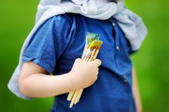 Cute little boy drawing with colorful paints in summer park. Creative child painting on nature. Outdoors activity for toddler kid. Talented toddler painter Stock Photos