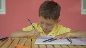 Cute little boy drawing in his album on wooden table