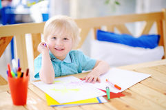 Cute little boy drawing and painting with colorful markers at kindergarten royalty free stock photo
