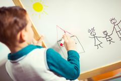 Cute little boy drawing on white board with felt pen and smiling Stock Images